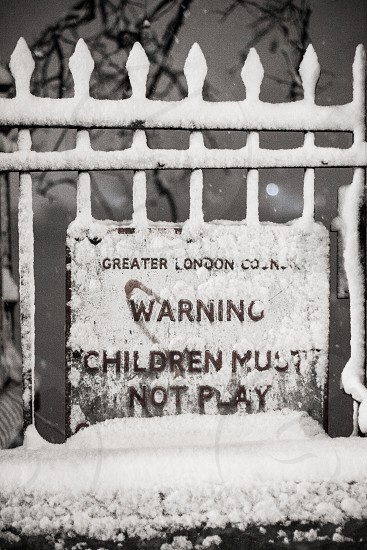 'Warning Children Must Not Play'. Street sign in the snow on The Embankment City of Westminster London UK photo