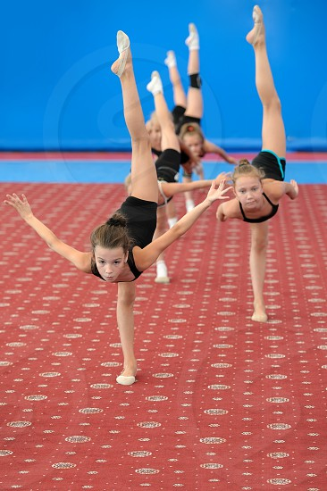 Group of girls exercising during gymnastic classes in the gym. They doing vertical leg-split photo