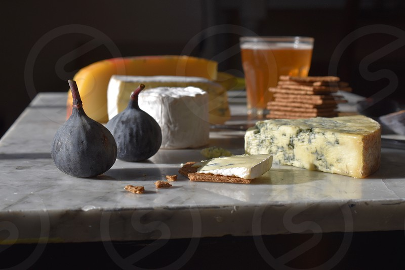 Selection of cheeses figs savoury biscuits and a glass of beer on a marble work surface. photo