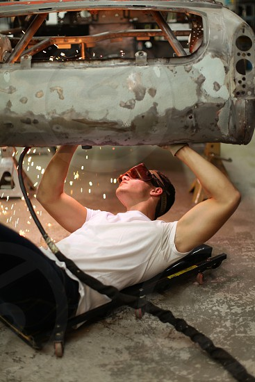 Man in white t-shirt welds the underside of a rusty car photo