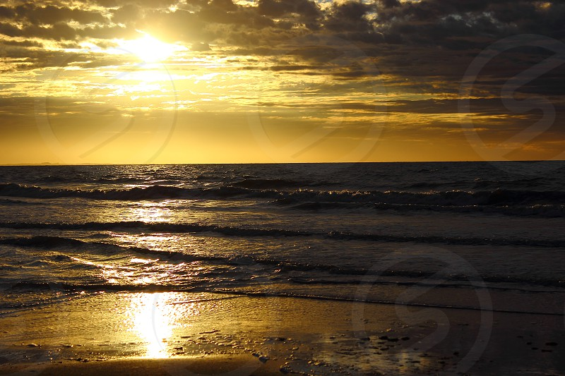 golden sunrise with sun reflection in the beach photo