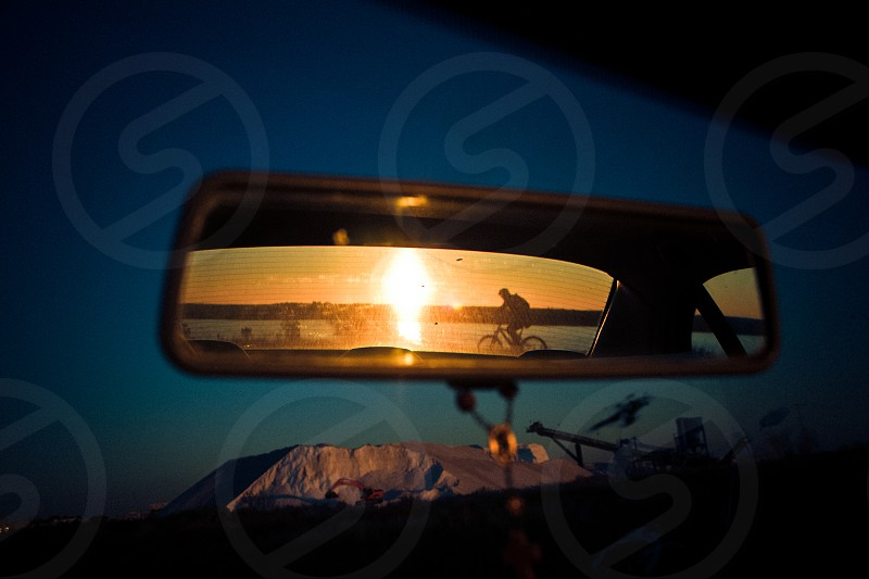 cyclist going past sunset in car rear-view mirror photo