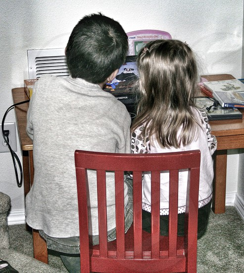 boy and girl sitting on red wooden chair in front of turned on laptop computer table on desk photo
