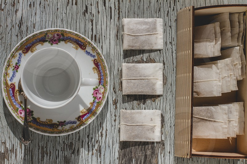 Cup of tea and tea bags arranged on wooden table photo