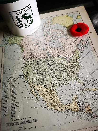 Antique map of North America with a poppy pin and Canada Moose candle holder photo