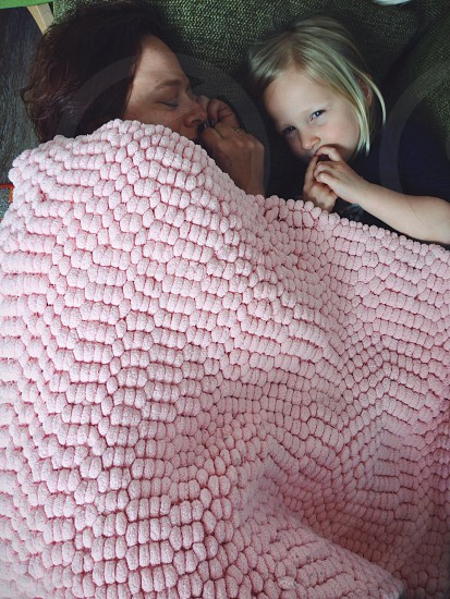woman and girl laying underneath pink blanket photo