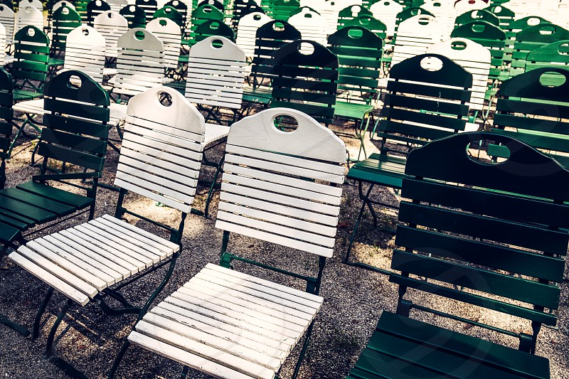 green and white painted retro wooden outdoor chairs lined in rows in park photo