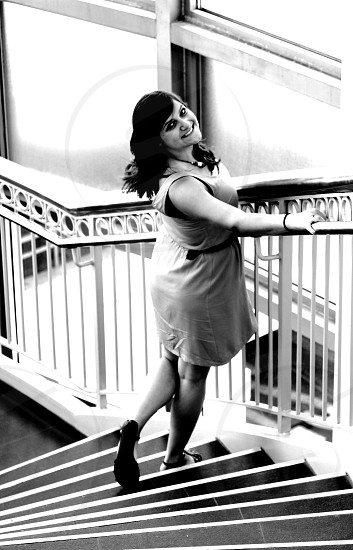 woman in sleeveless shift dress standing beside staircase hand rails in grayscale photo
