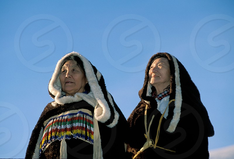 Two Inuit women from Nunavut who are traditional throat singers are dressed in fur parkas and mukluks pose in a wintery landscape  photo