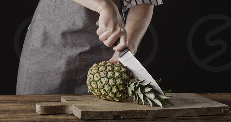 Chef girl in an apron cur juicy tropic fruit pineapple on two parts on a wooden cutting board on a kitchen table on a black background. Motion 4K UHD video 3840 2160p. photo
