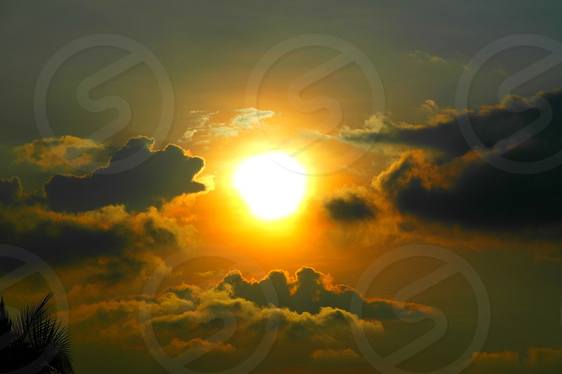 sun with clouds beside photo