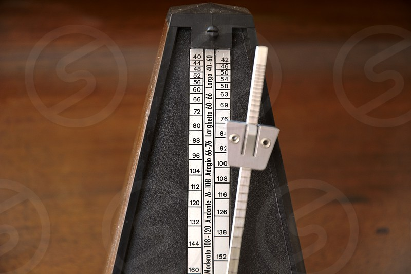 Close up of a vintage metronome with swinging pendulum photo