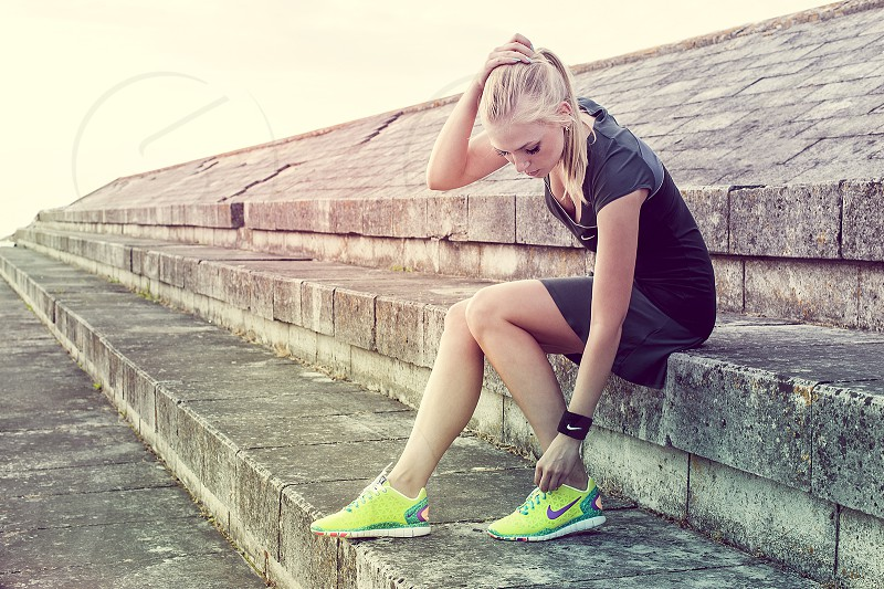 woman sitting wearing yellow and green nike shoes photo