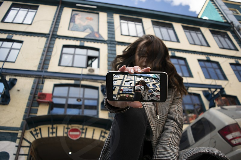 Female model showing the screen of her smartphone recursion low angle shot. photo