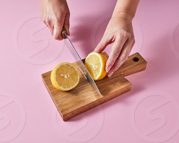 On a wooden board the hands of a woman cut a ripe lemon for making a vitamin drink around a pink background with space for text. photo