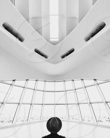 low angle grayscale photo of a person wearing hat inside building photo
