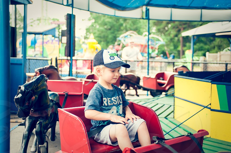 boy youth child ride fair carnival amusement park horses carriage buggy circles red yellow blue green cap hat blonde kid fun happy carousel around summer photo