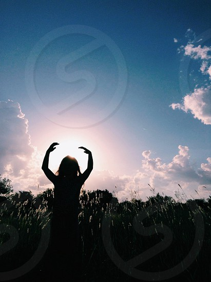 woman standing in field blue sky white clouds photo