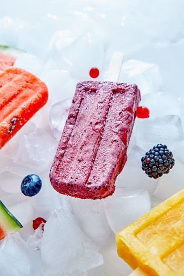 Fruit frozen juice on a stick presented on ice cubes with blueberries currants and blackberries. Summer dessert. Top view photo