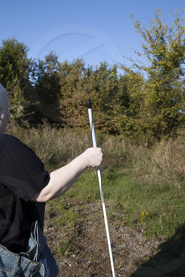 Person holding walking cane in nature photo