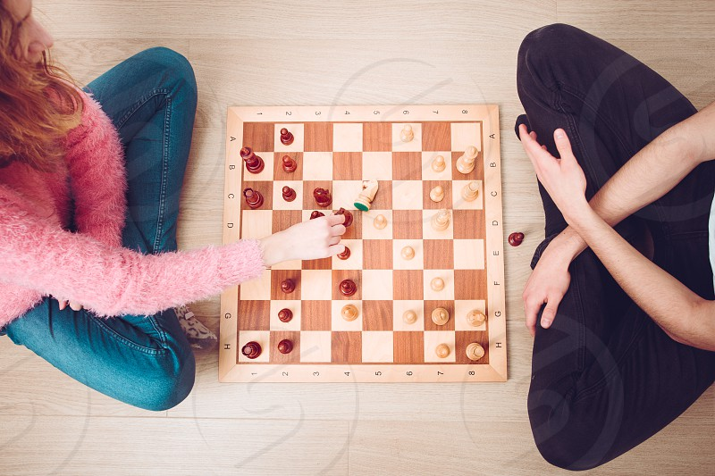 Girl and boy playing chess at home. Girl moving her piece and capturing her opponents knight. Teenagers sitting on a floor. View from above. Copy space for text at the top and bottom of image photo