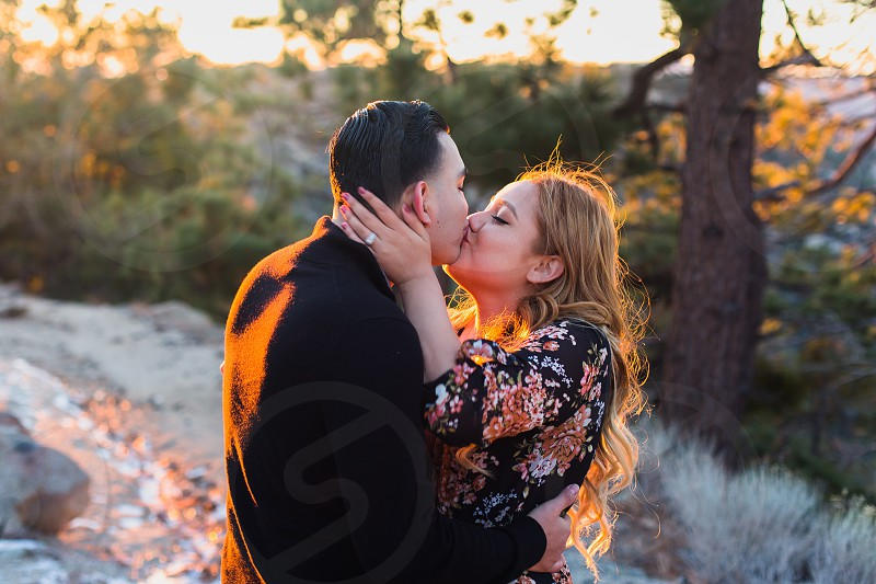 Kiss couple engaged mountains backlight ring love photo