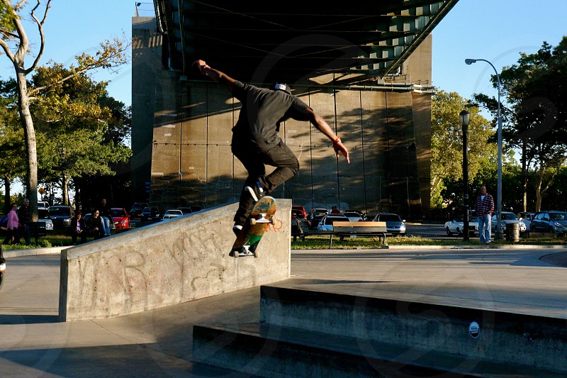 person making stunt with skateboard near trees photo