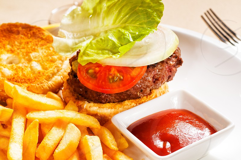 fresh classic american hamburger sandwich with french fries and ketchup sauce on side photo