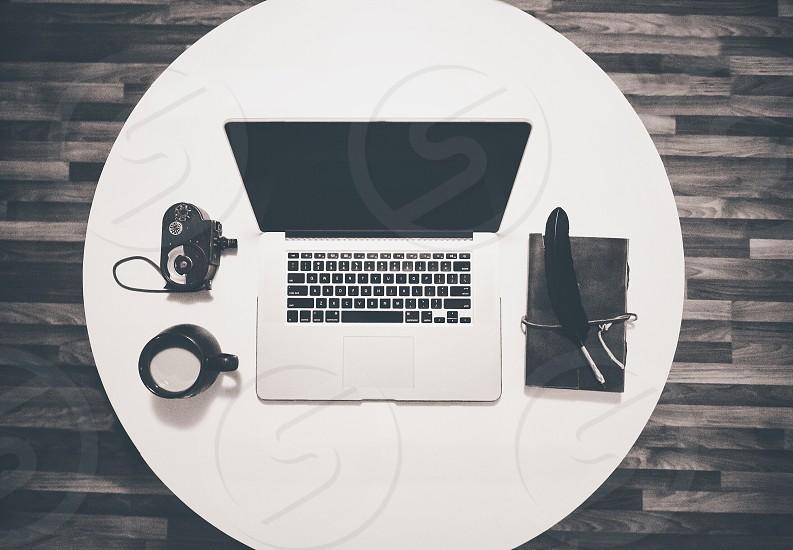 macbook pro on white round table photo