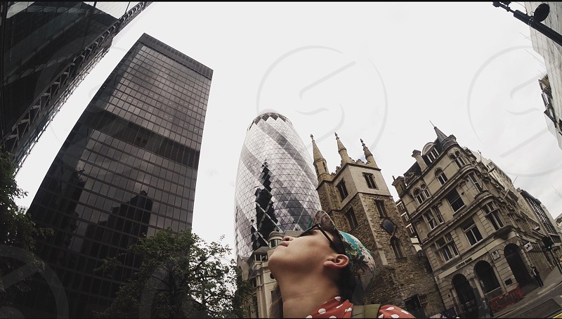 woman standing outside looking up at sky with skyscrapers in background photo