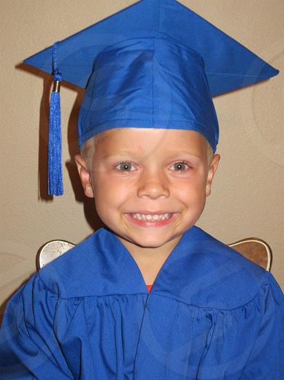 boy smiling wearing blue graduation dress photo