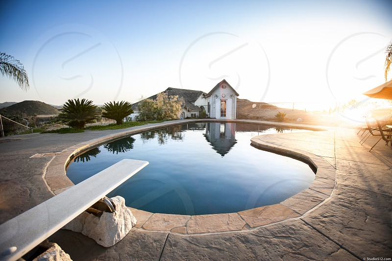 A private backyard and pool house.  Swimming diving board sunset umbrella custom. photo