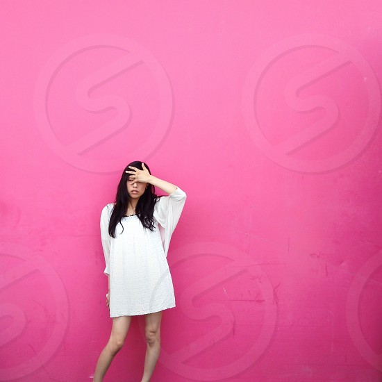 In front of the pink wall photo