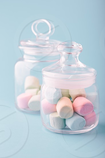 Jar filled with colorful marshmallows on plain background photo
