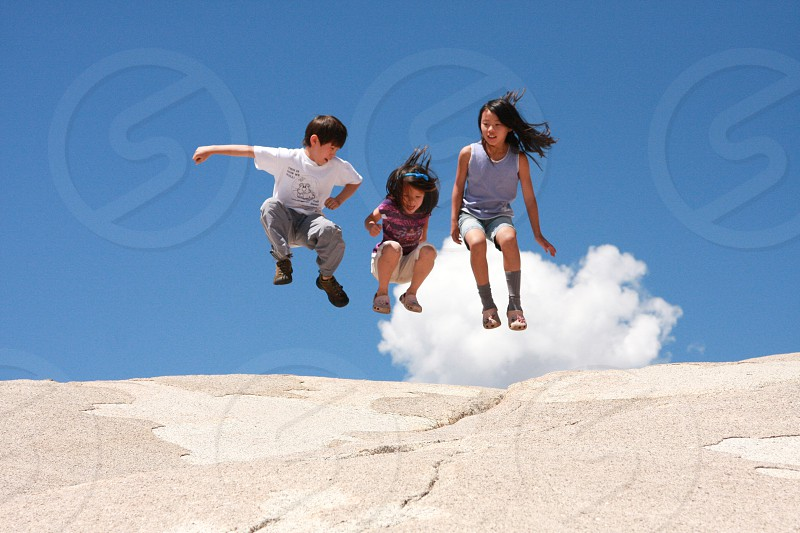 Three kids jumping in the air with a blue sky and white cloud in the background.  photo