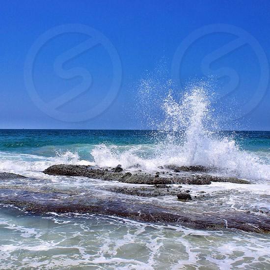 ocean wave hitting rock formation photo