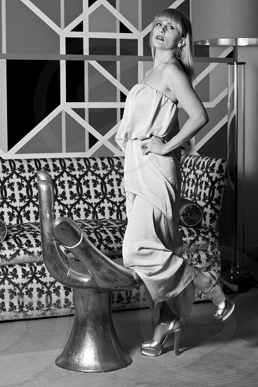 woman in ruffled tube dress standing by a hand chair in grayscale photo
