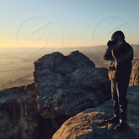 person wearing a brown jacket taking pictures from top of a mountain  photo