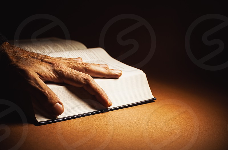 Conceptual composition about knowledge male hand on open book. photo