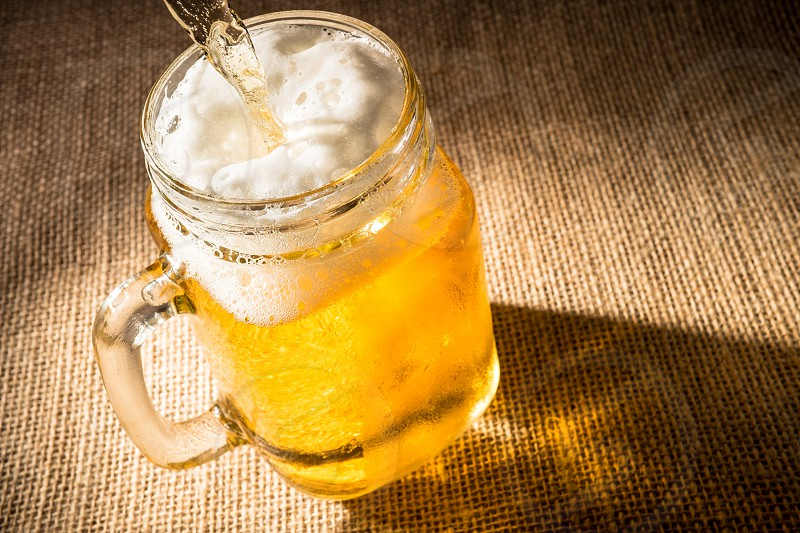 Beer is poured into a glass mason jar. photo