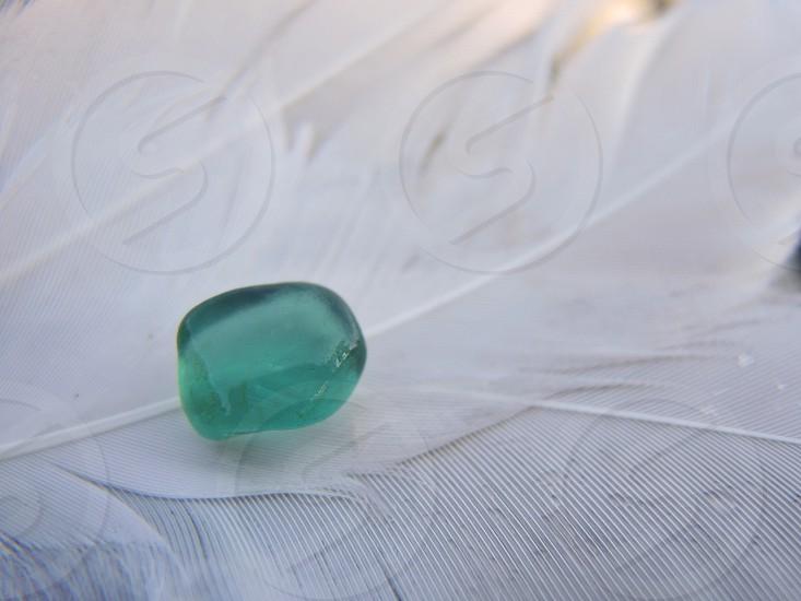 green stone on white feather photo