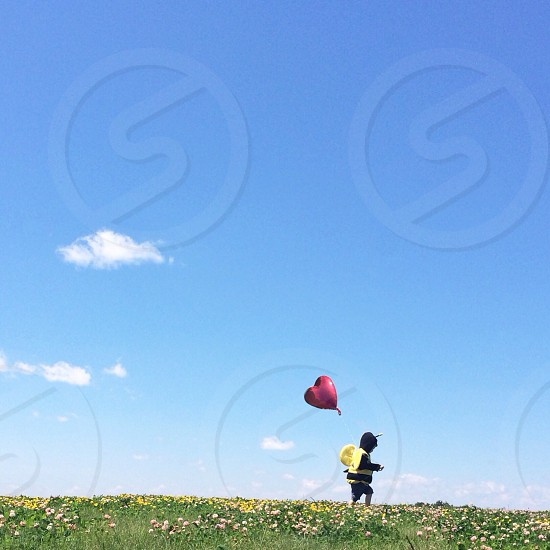 child in black and bee costume with red heart balloon flower field photo