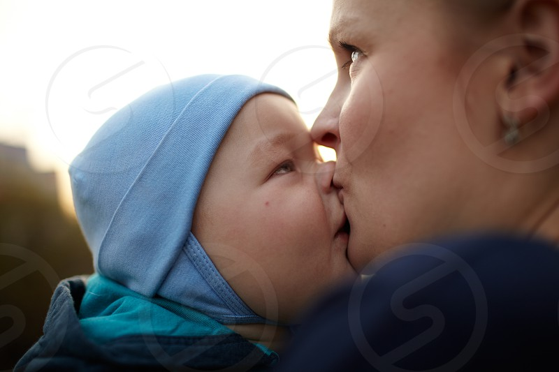 Little boy kissing his mom. Natural light real colors shallow DOF (prime 35mm L lense). photo
