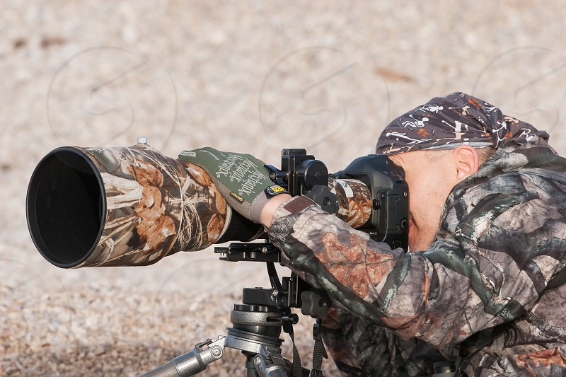 Creative photographer using big telephoto lens photographing birds wearing camoflage pattern clothes photo