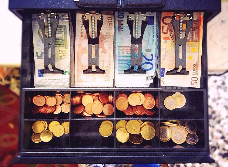 assorted euro bills and coins in cash register photo