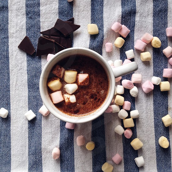 white ceramic mug filled with brown chocolate on top with marshmallows and some marshmallows and chocolate crumbles on white and blue stripe textile photo