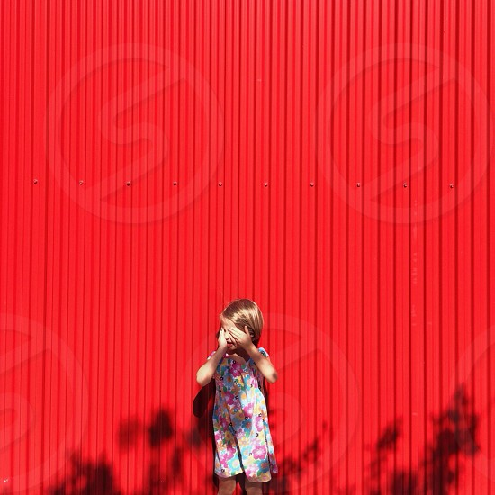 blonde girl in a pink floral jumper standing by a red wall photo