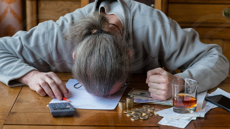 Close up man with calculator counting making notes at home hand is writes in a notebook. Stacked coins arranged at deesk. Savings finances concept. Businessman in panic. Stress at work. photo