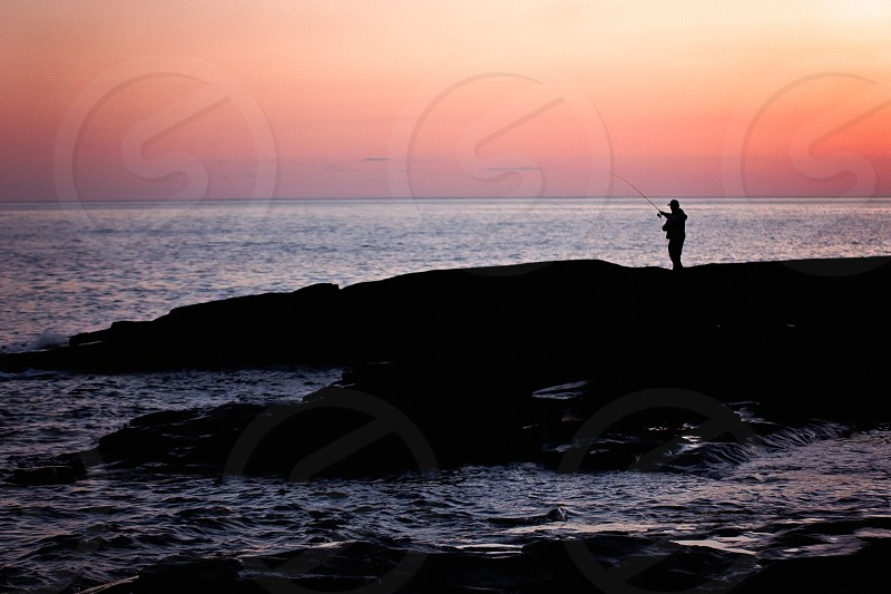 A silhouetted man fishes during an orange sunset over Lake Superior photo