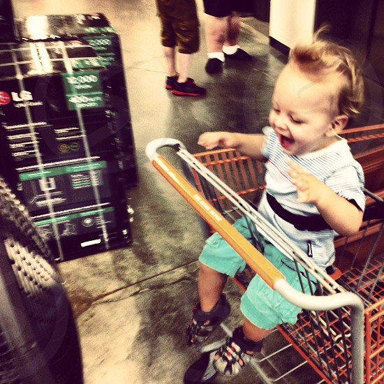 kid sitting on grocery cart photo